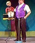 """Dave Mitchell demonstrating ventriloquism. Mr. Magish proves his versatility with an excellent demonstration of ventriloquism, both with a traditional ventriloquism figure (pictured), as well as breathing new life into an old magic routine, the Genie in a Bottle, as well as his """"revenge"""" on Juggles/Lee Mullaly, with a Mortimer Snerd-style character, """"Homer"""", which was really a rubber mask worn by Lee."""