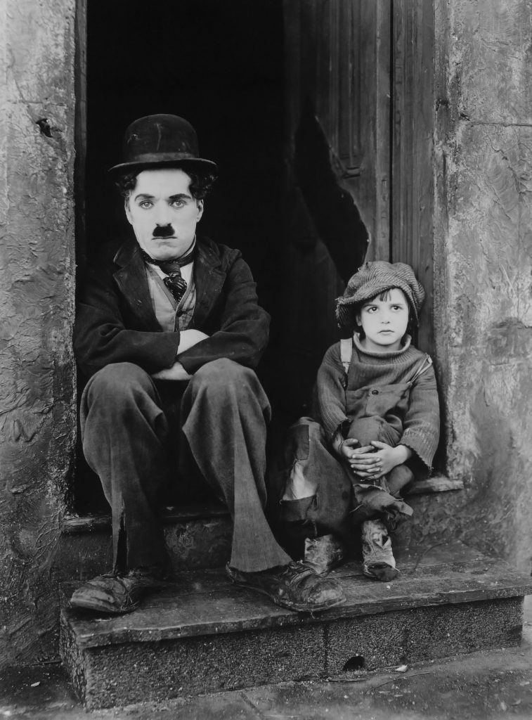 Famous image from The Kid with Charlie Chaplin and Jackie Coogan sitting on a doorstop.