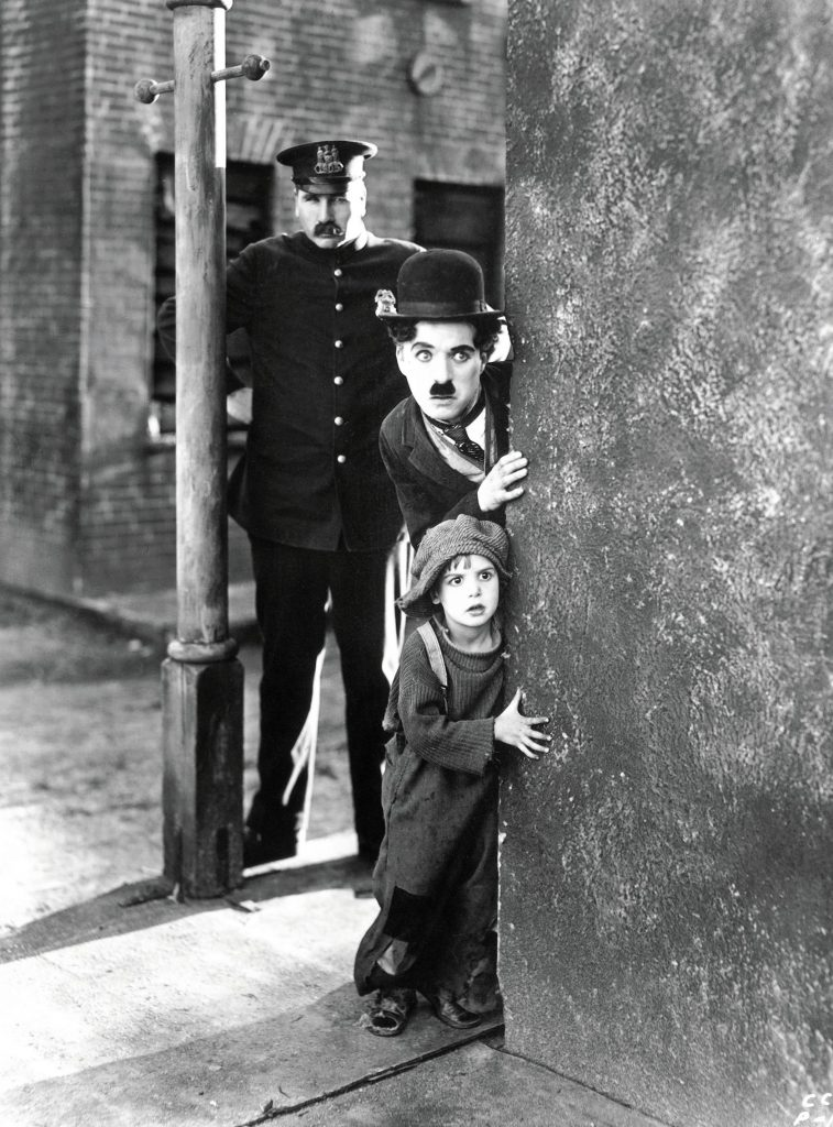 A famous image from Charlie Chaplin's first feature-length film, The Kid – with Charlie Chaplin leaning over Jackie Coogan (the Kid), with an interested police officer in the background watching them both.
