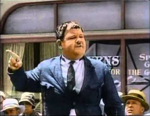 Colorized photo of Oliver Hardy auctioning off the boys' car in One Good Turn