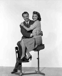 Red Skelton and Esther Williams on a school desk in a publicity photo from Bathing Beauty